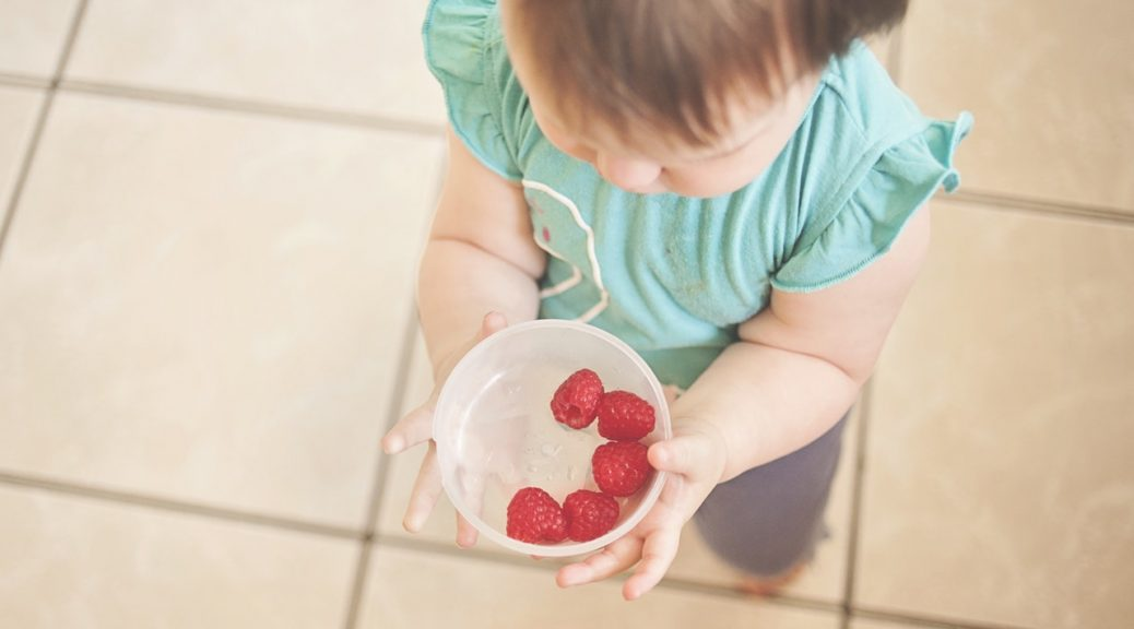 preventing picky eating: toddler holding a bowl of raspberries